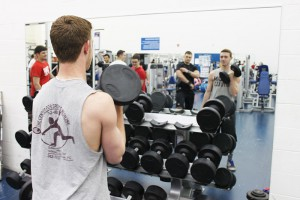 student lifting free weights