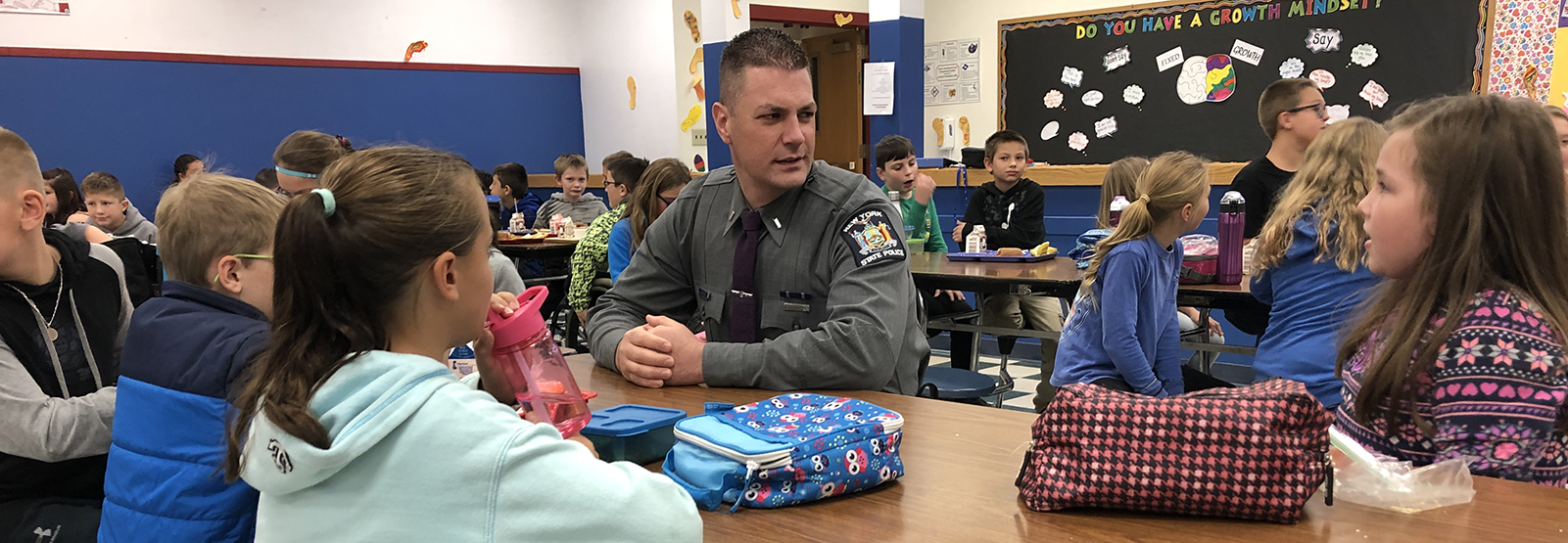 officer sits with students at lunch table