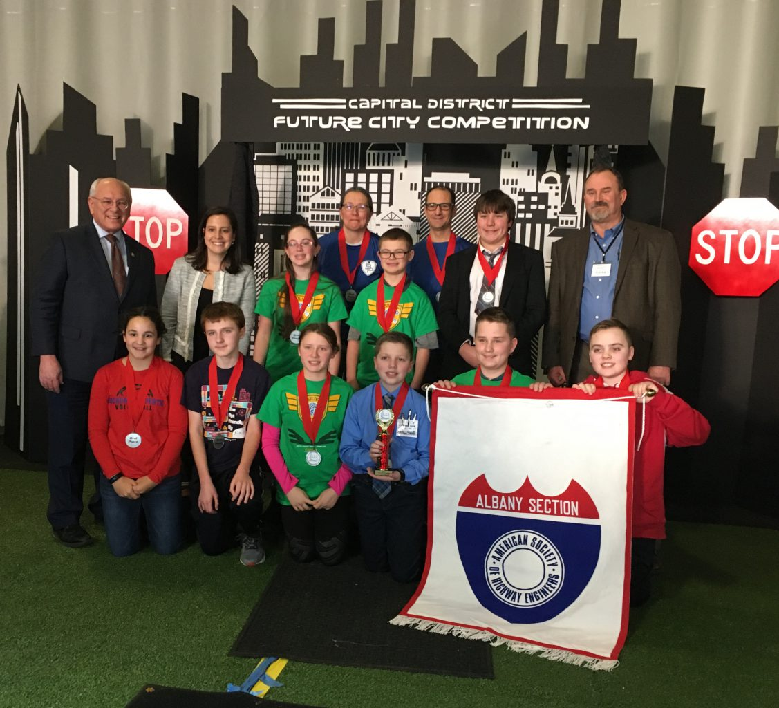 federal legislators pose with a group of middle school students wearing medals. two students hold a banner