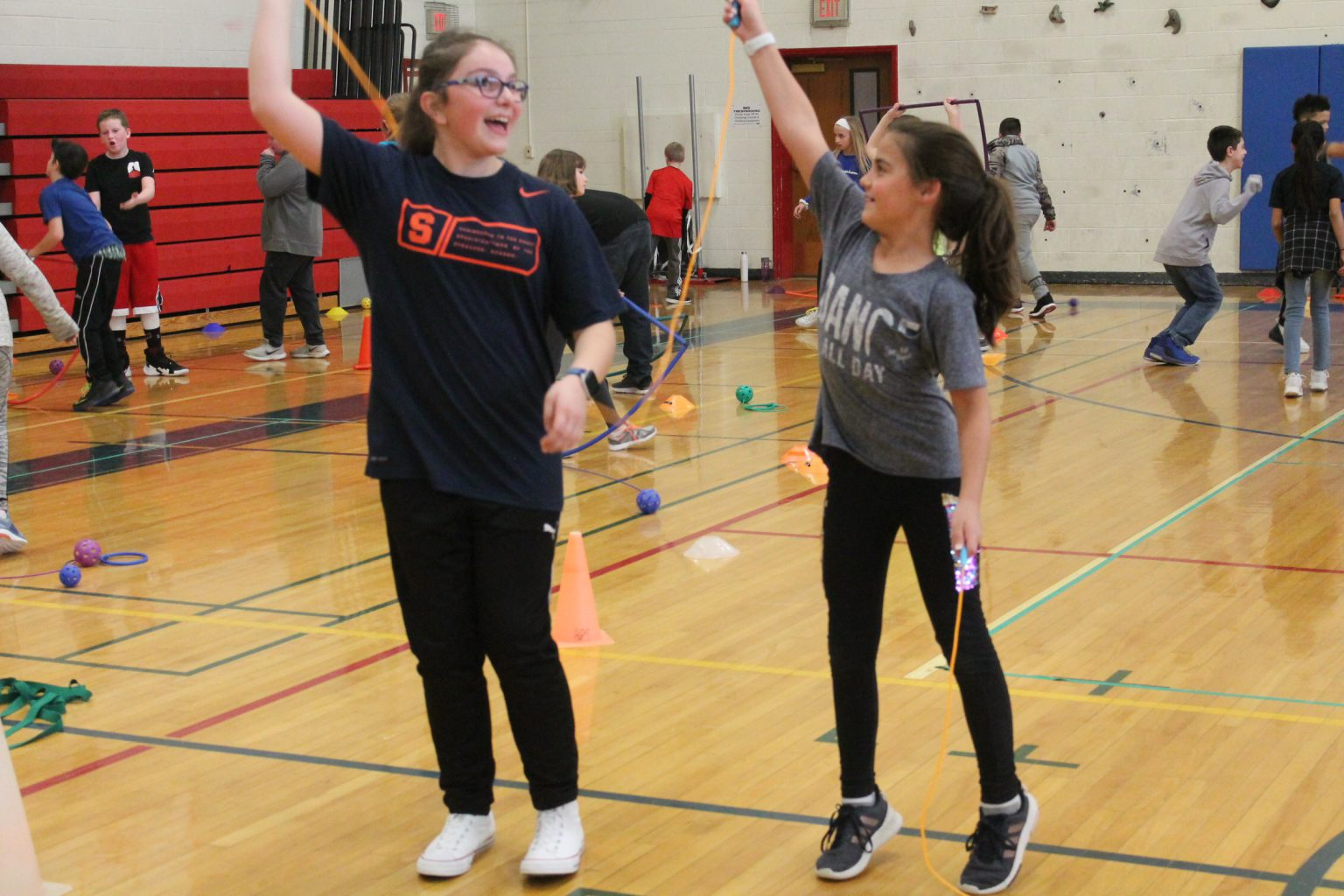 two girls help each other jump rope