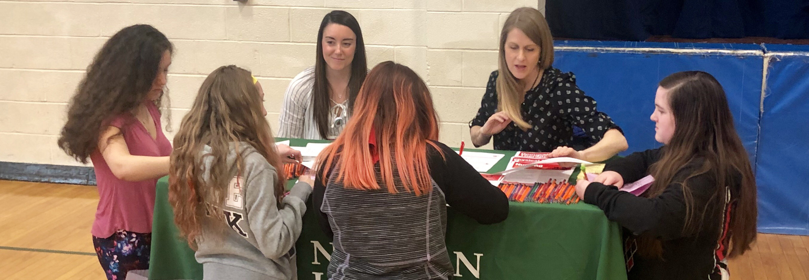 students talk with adults at a table during a career fair