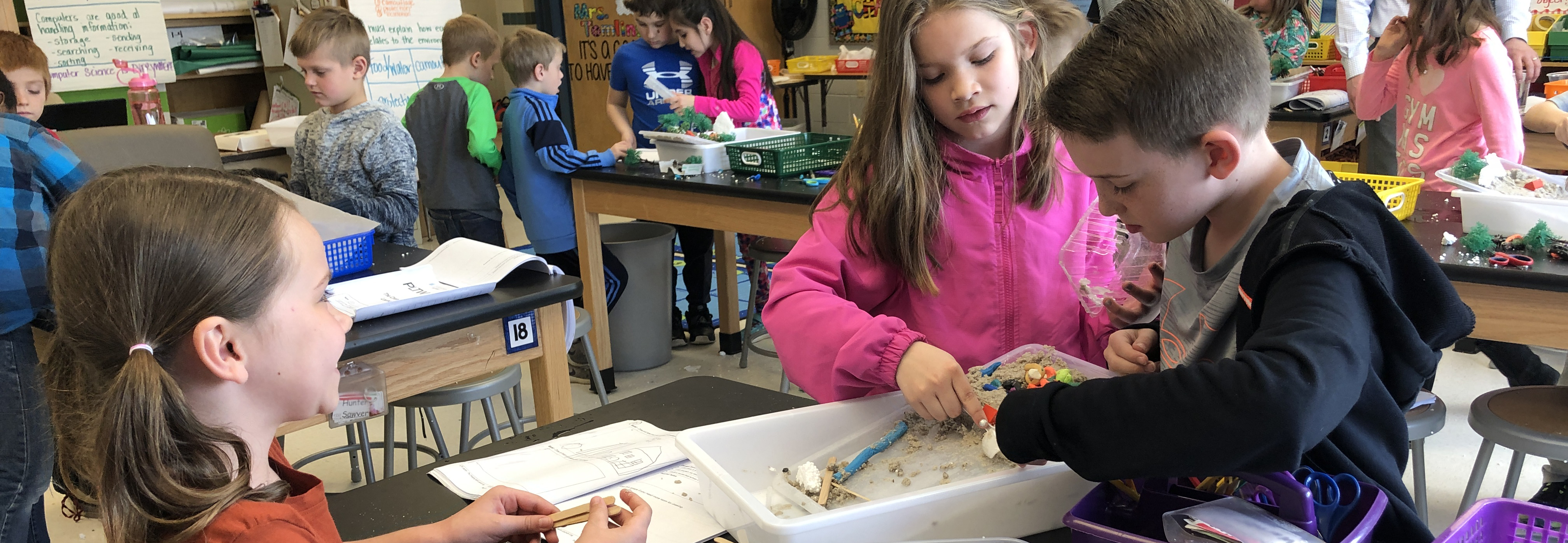 three students collaborating around a tray with building materials