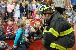 a firefighter speaks to students during a fire safety demonstration