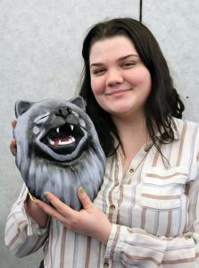 student holds a sculpture of her dog's face