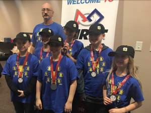 man stands with six fifth-graders wearing baseball caps and medals