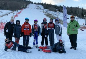 teens and adults in ski gear on skis on the snow