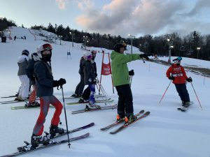 group of kids on skis on the hill