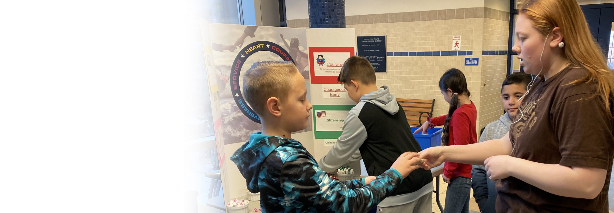 a younger and older student complete a transaction in a school lobby