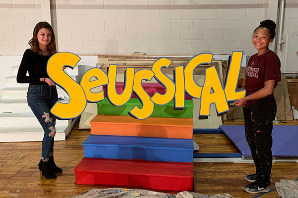 "Ashley Marotta and Olivia Fraser hold the set piece that says ""Seussical"""