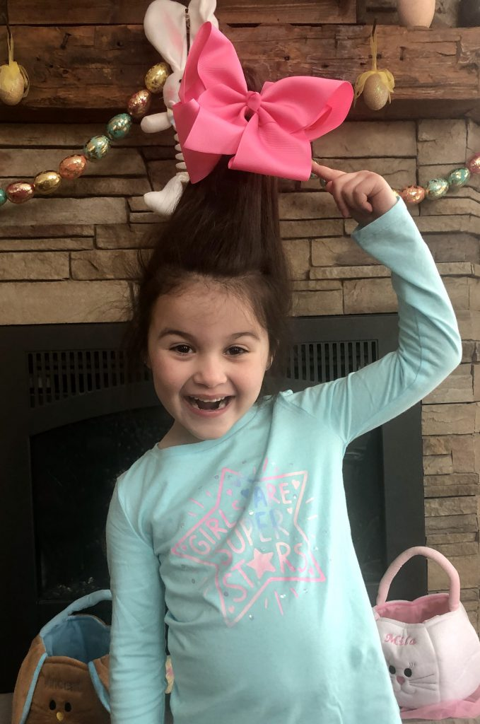 girl pointin at huge pink bow