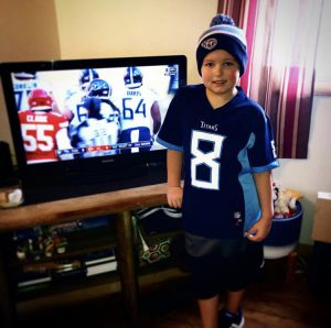 boy watching football in team jersey and hat