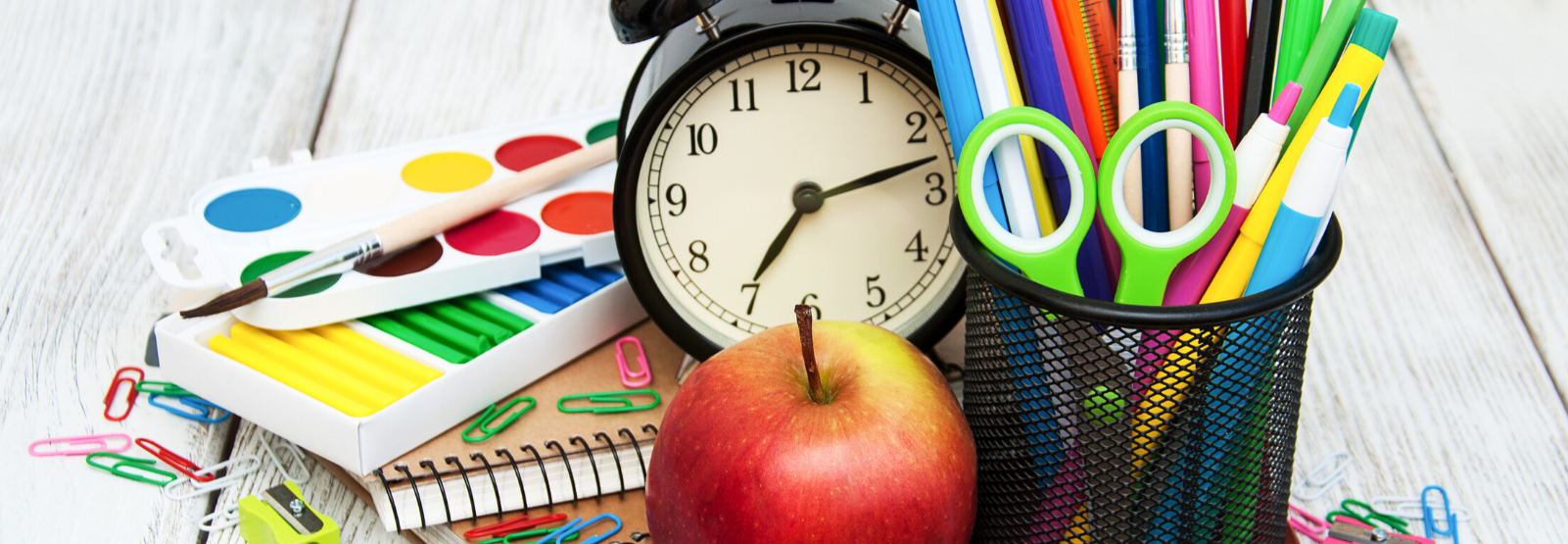 school and art supplies, an alarm clock and an apple