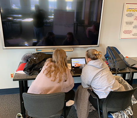 Emily Macfarlane and Meaghan Uhlinger work on computer