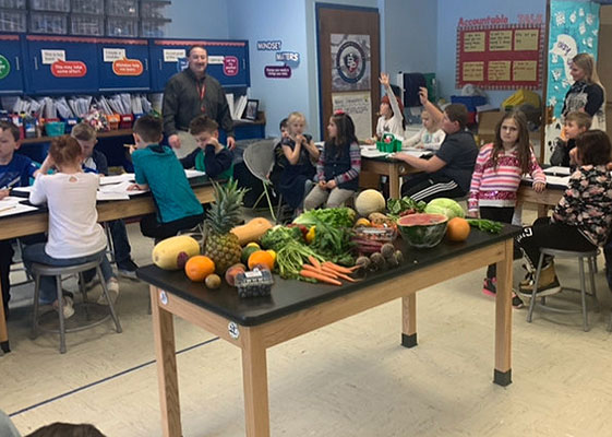 students in classroom with a table filled with vegetables and fruit
