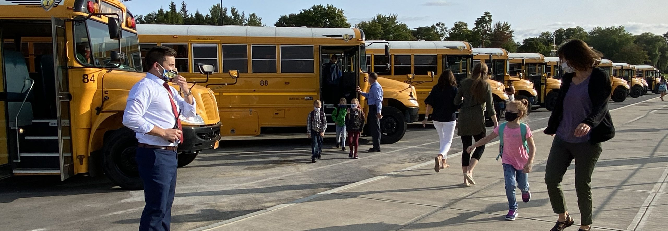 adults and children on a sidewalk in front of a row of parked buses