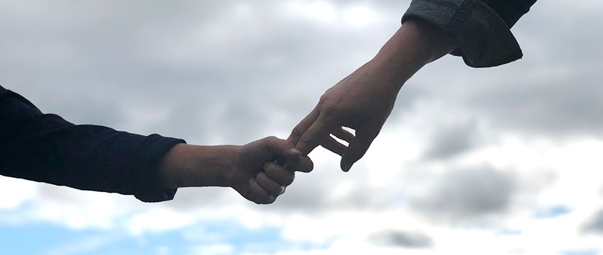 photo of an adult and a child holding hands