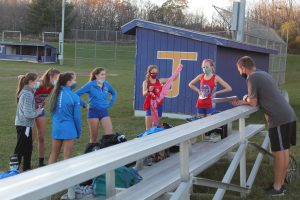 B-P cross country coach stands with the girls team prior to the start of a recent race..