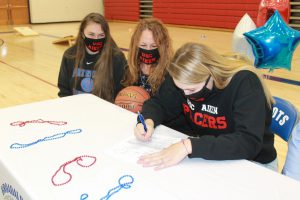 Makenzie Smith signs her National Letter of Intent as her mother and sister look on.