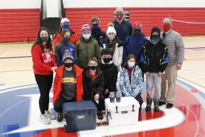 Members of the B-P alpine ski team pose inside the B-P high school gym with athletic director Tucker Gifford and head coach Shawn Cotter, in front of two Yeti coolers and two Yeti travel mugs that were recently raffled off as a team fundraiser.