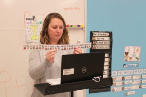 A woman holds up a graphic to help teach the alphabet to remote pre-k students.