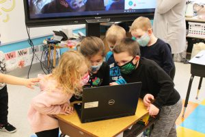 Five pre-k students with masks on look into their teacher's computer screen to say hello to their classmates who are learning remotely.