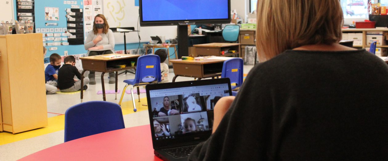 A teaching assistant teaches remote children on Google Meet, while another teacher simultaneously teaches in-person students in antoher section of the classroom.