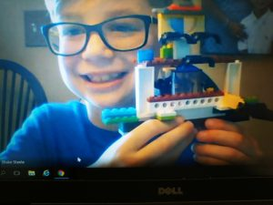 a smiling boy with glasses shows off a lego creation