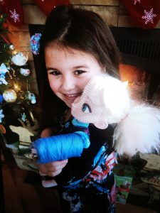 a young girl shows off a cast that she made and applied to her doll