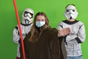 a female high school student dressed as a Jedi stands in front of a green screen, flocked by two students dressed up as Storm Troopers.