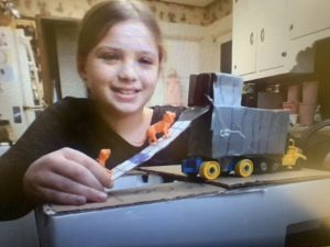 a smiling girl shows off a contraption that she created with tiger figurines climbing up a ramp into a truck.