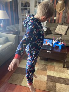 A remote PE student participates with an interactive video, whil wearing his pajamas at home.