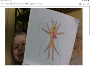 A remote art learner shows her finished project of a Vitruvian Mannequin Snow Angel to the computer camera.