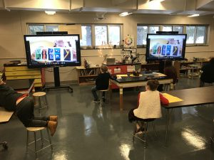In-person art students at BPES interact with their classmate who are learning remotely, using a large screen at the front of the classroom.