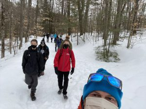 An adult wearing a face mask, winter hat and sunglasses takes a selfie of students hiking behind him.