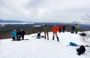 Ten people, all wearing winter gear, are shown standing in the snow at the summit of Cat Mountain, with Lake George shown in the distance behind them.