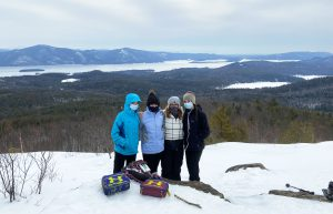 Four students wearing winter gear are shown standing in the show at the summit of Cat Mountain, with Lake George shown in the distance behind them.