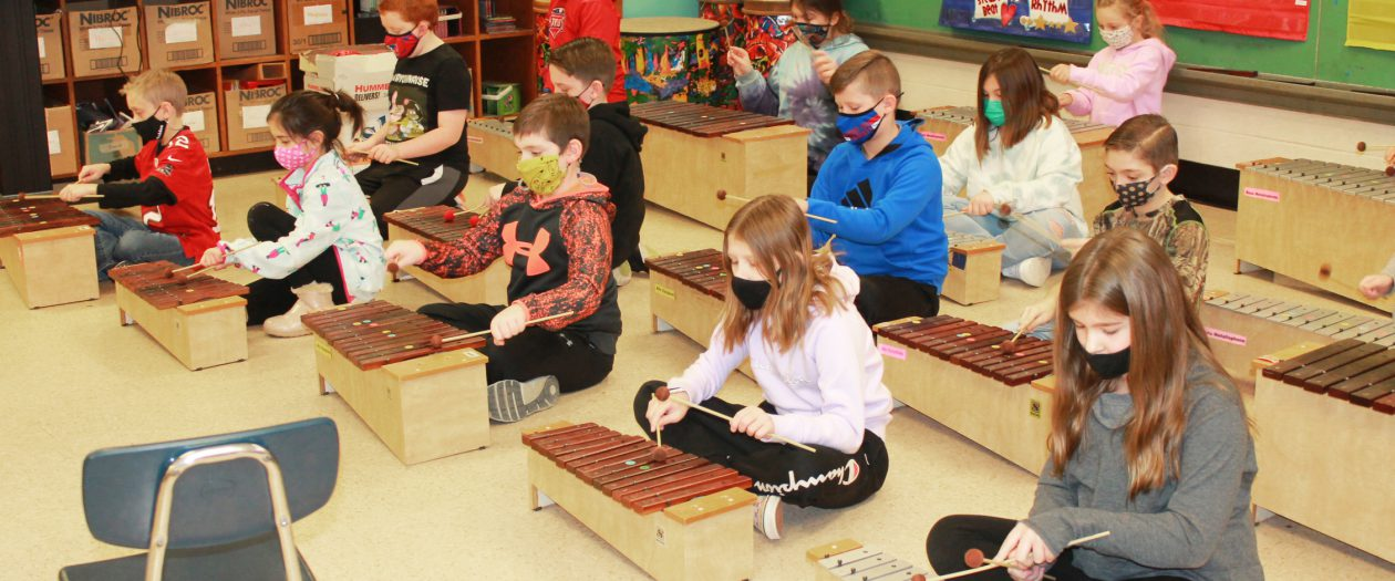 Children at BPES play xylophones in their music classroom.