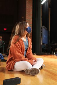 A young actress sits on the stage awaiting instructions at play rehearsal.