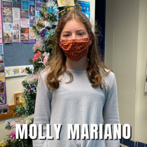 """a young firl wearing a mask poses in front of an artificial tree, with her name posted at the bottom, """"Molly Mariano."""""""