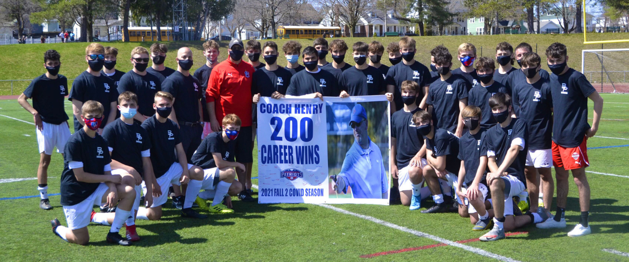 The B-P boys varsity soccer team poses on the soccer field with head coach Brian Henry, holding a white sign commemorating his 200th win.