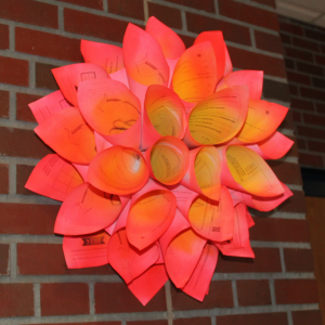 a pink and yellow paper flower hangs on a brick wall in a hallway at B-P Junior/Senior High School.