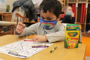 a young boy with black hair and a rainbow mask on uses crayons to fill in an assignment.