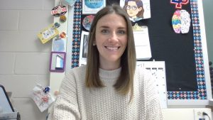 a woman with brown hair, wearing a white sweater, sitting at a desk, smiles to the camera.