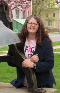 a soman wearing a black sweater and pink shirt poses next to a large bell
