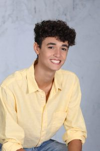 a young man wearing jeans and a yellow button down shirt, with dark curly hair, poses for a professional photo.