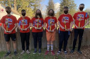 six students wearing red shirts, holding trophies and wearing face masks pose outside.