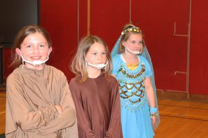 three young actresses from Aladdin Kids listen to the director give instructions during a rehearsal