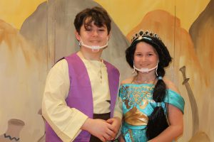 a young boy dressed as Aladdin and a young girl dressed as Jasmine pose in front of set scenery