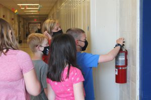 a student plans where to stick googly eyes on a fire extinguisher in the hallway of the school.