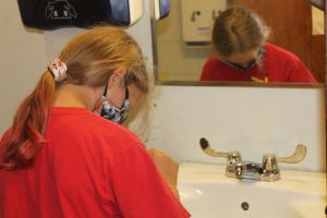 a student is shown strategically placing googly eyes on the faucet in a restroom.